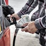 Man met geld in de hand pakt een benzineslang